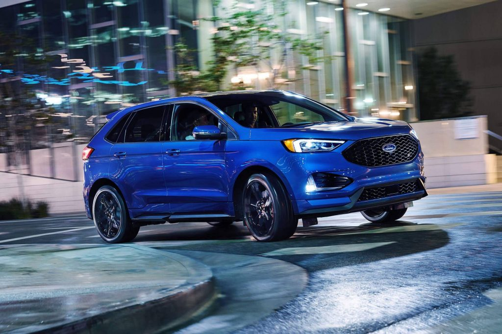 Blue Edge Ford SUV driving around curve at night