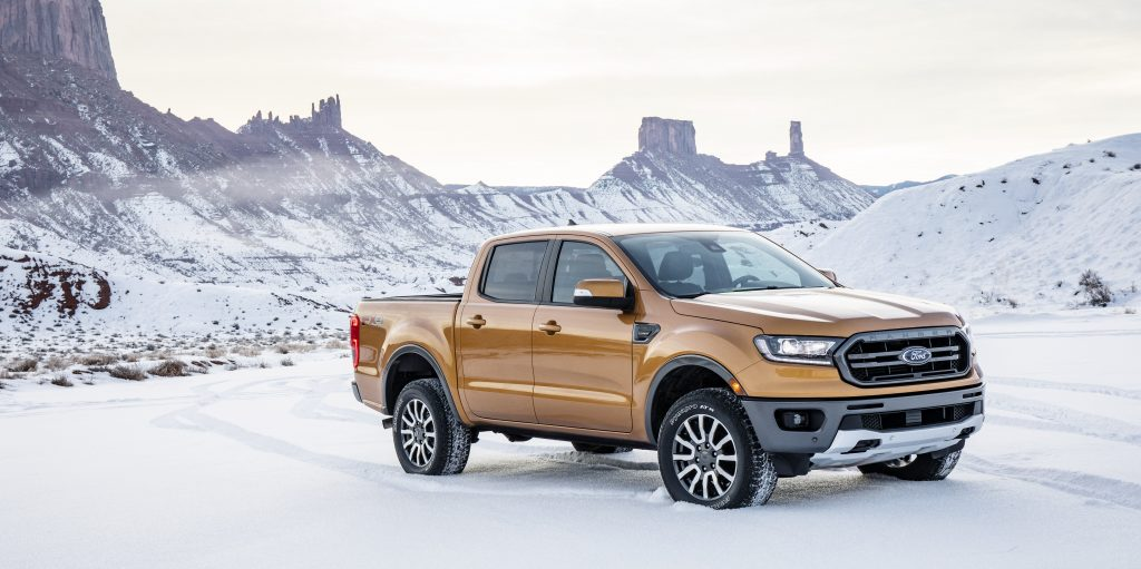 An orange crew cab 2019 Ford Ranger is parked in front of snow-covered mountains