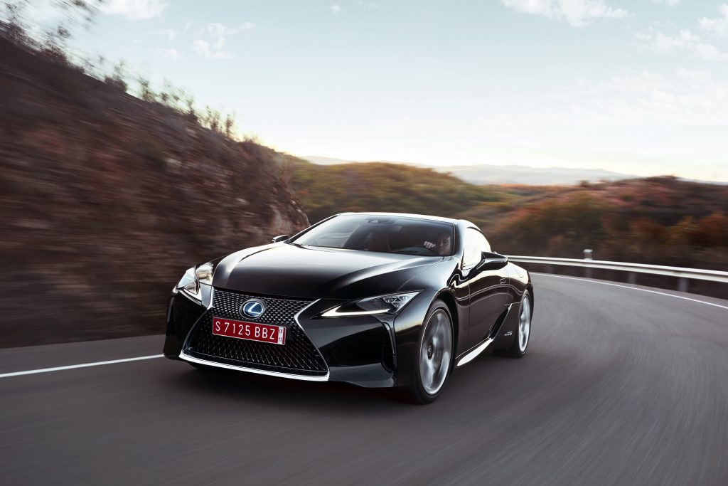 The Lexus LC 500h at speed on a winding scenic road