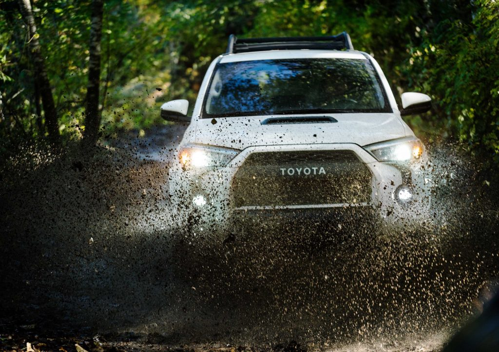 a white off-riding TRD Pro trim Toyota 4Runner splashes through the mud on an off-road trail in the woods