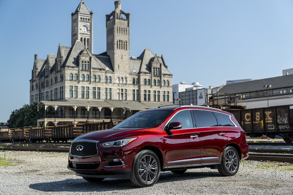 A red 2019 Infiniti QX60 Limited driving around the city.