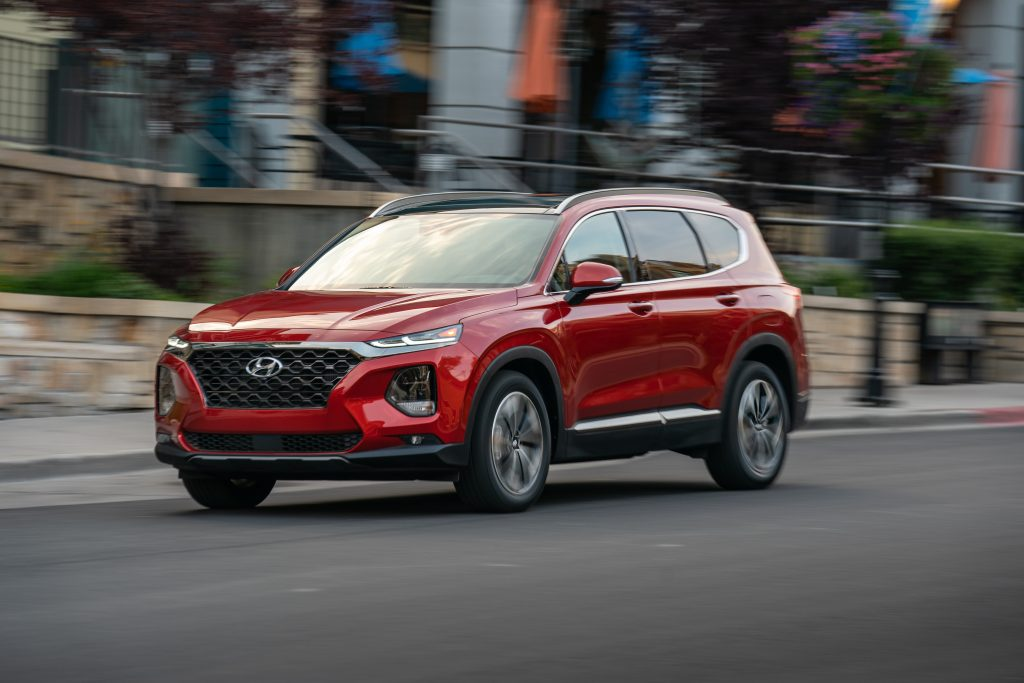 red Hyundai Santa Fe in motion down city street