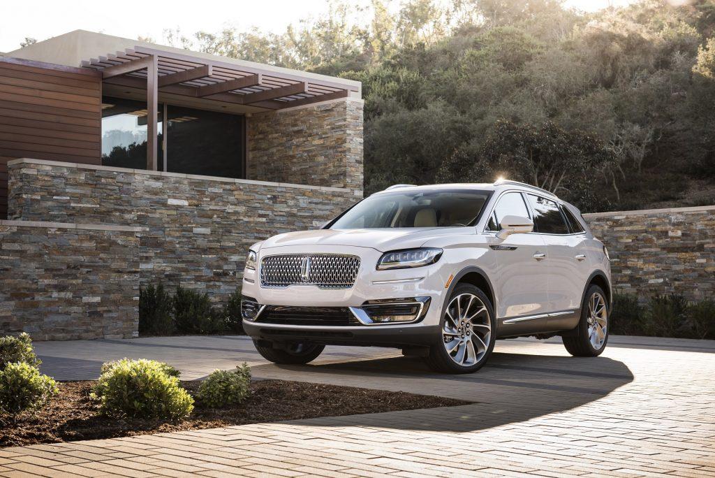 A white Lincoln Nautilus sits on a brick driveway.
