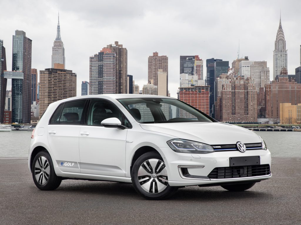 White 2017 Volkswagen e-Golf hatchback in front of a city skyline