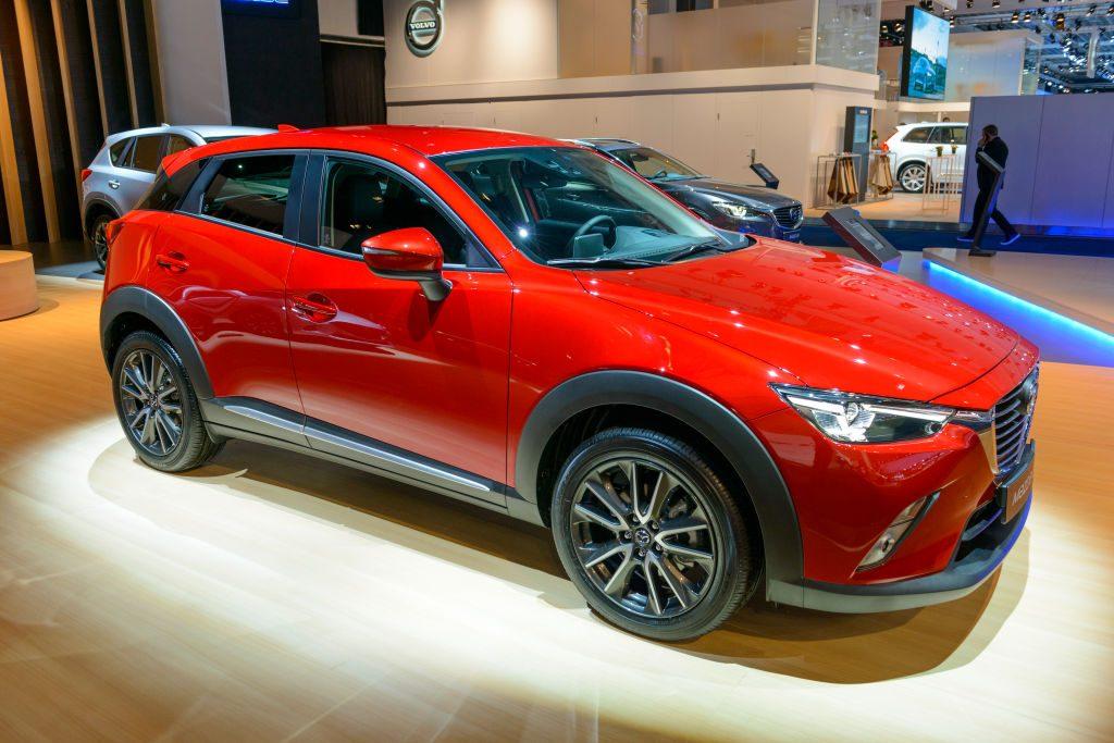 A red Mazda CX-3 in a showroom.