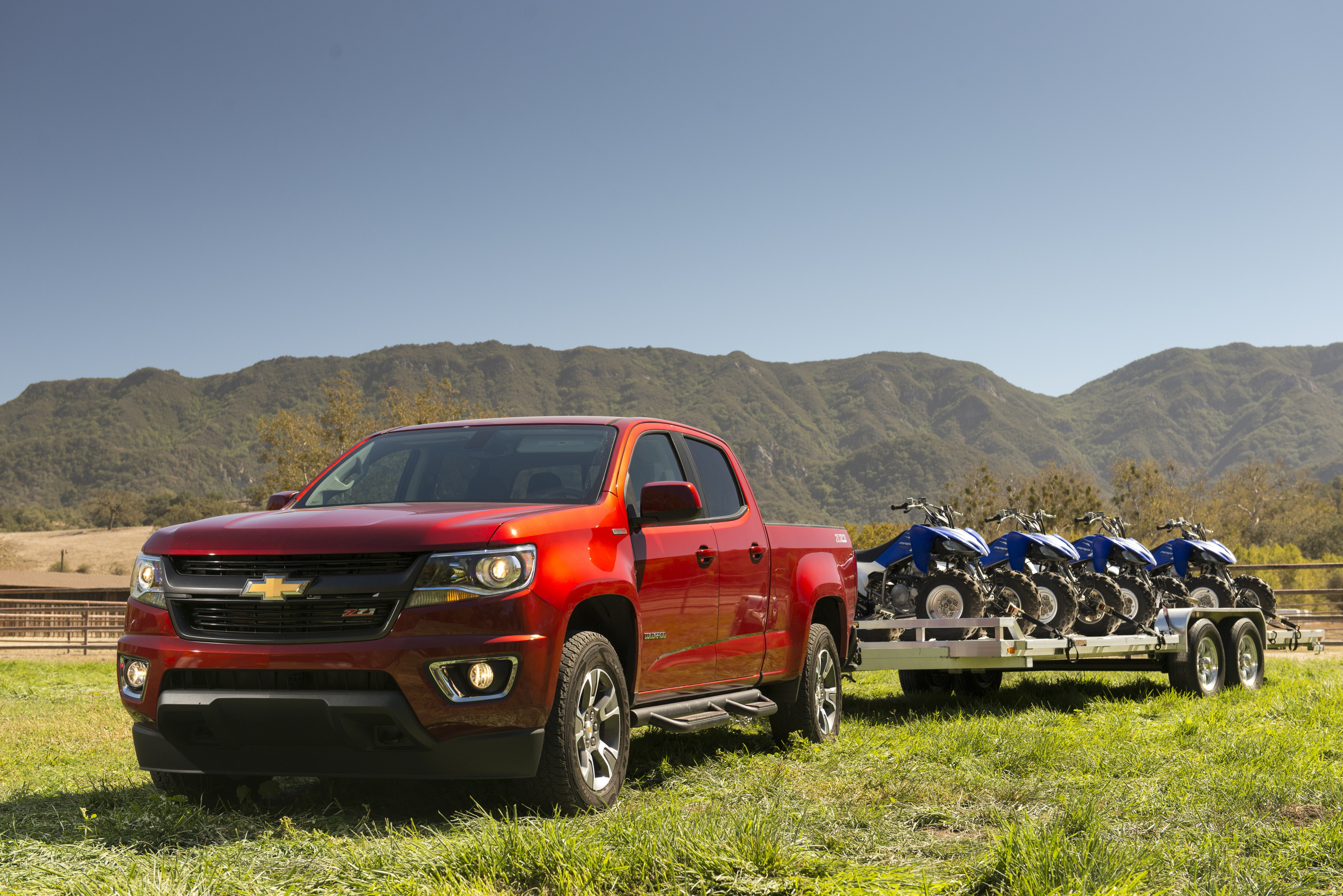 a 2018 chevrolet colorado showing off its small truck diesel power by towing a trailer loaded with 4 ATVs
