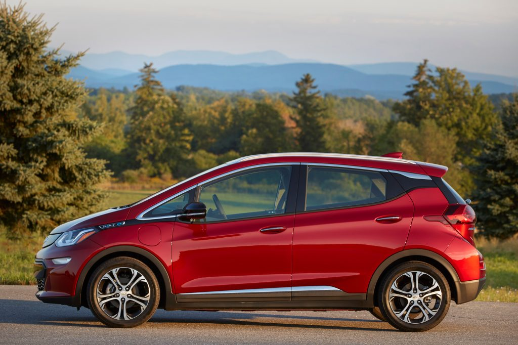 A red Chevy bolt parked before trees and a mountain