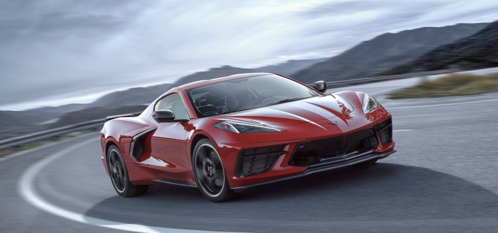 A red 2020 Chevy Corvette rounds a scenic turn.