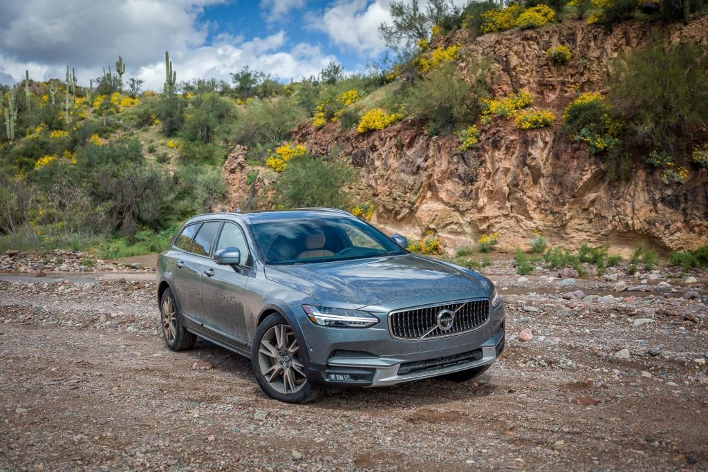 A grey Volvo V90 parked near the forest.