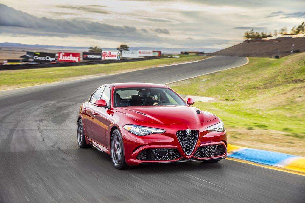 A red Alfa Romeo Giulia Quadrifoglio speeding through a turn on a race track.