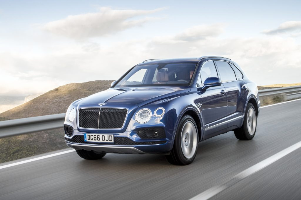 a blue Bentley Bentayga SUV at speed on a scenic road