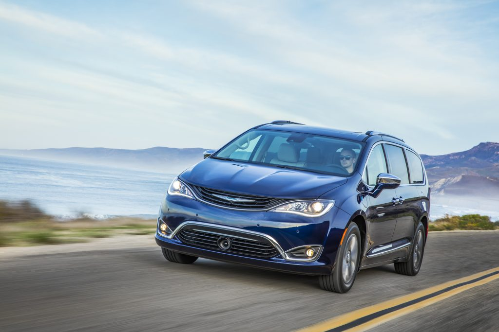 a dark blue Chrysler Pacifica hybrid at speed on a scenic road is one example of brands competing in the hybrid segment
