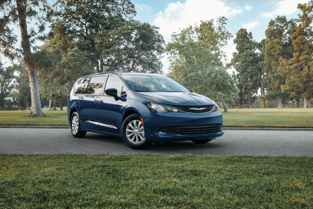 A blue Chrysler Voyager minivan parked on street