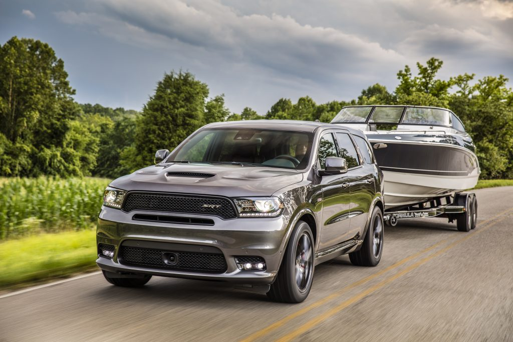 2019 Dodge Durango SRT towing a boat down a country road