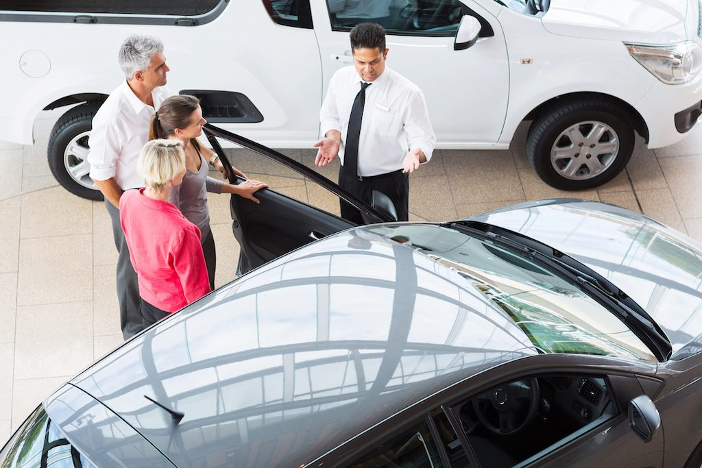 View of car salesman showing vehicle to family
