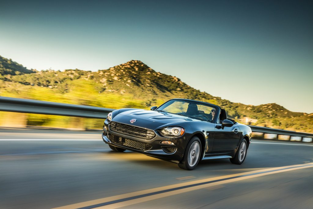 A 2019 FIAT 124 Spider driving down a desserted highway.