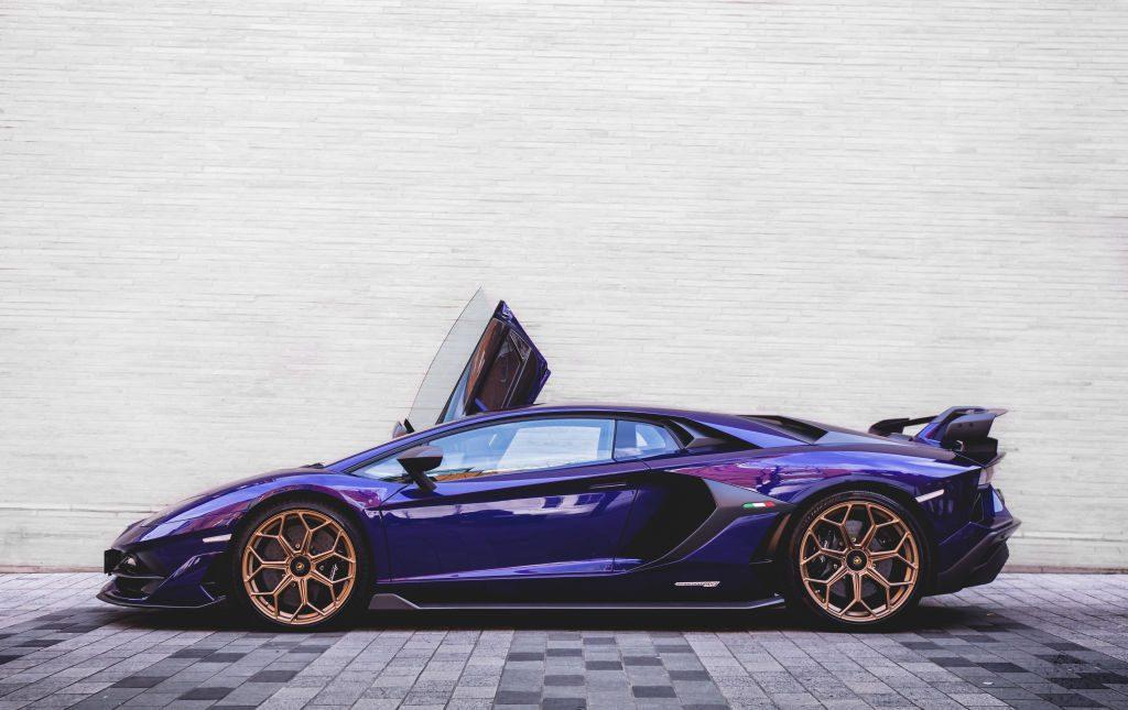 A purple 2019 Lamborghini Aventador SVJ parked in an alley.