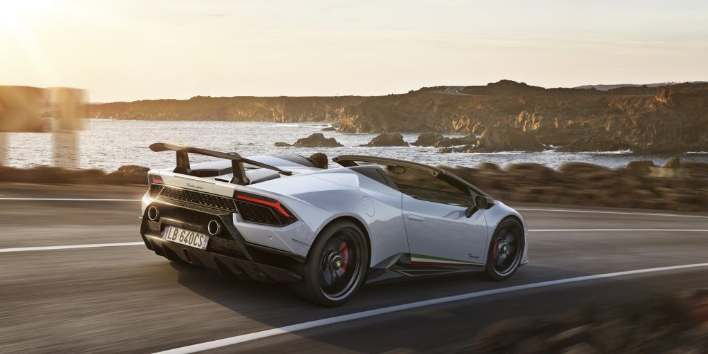 A white Lamborghini  Huracan Preformante Spyder driving down a coastal road