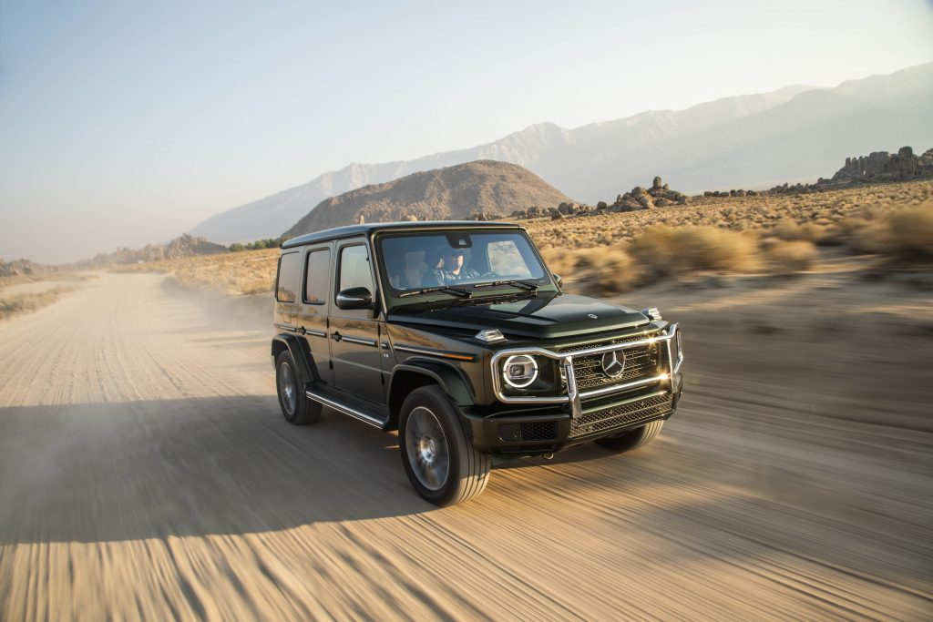 A black G-Wagon driving fast in the sand, making use of its twin-turbo V8
