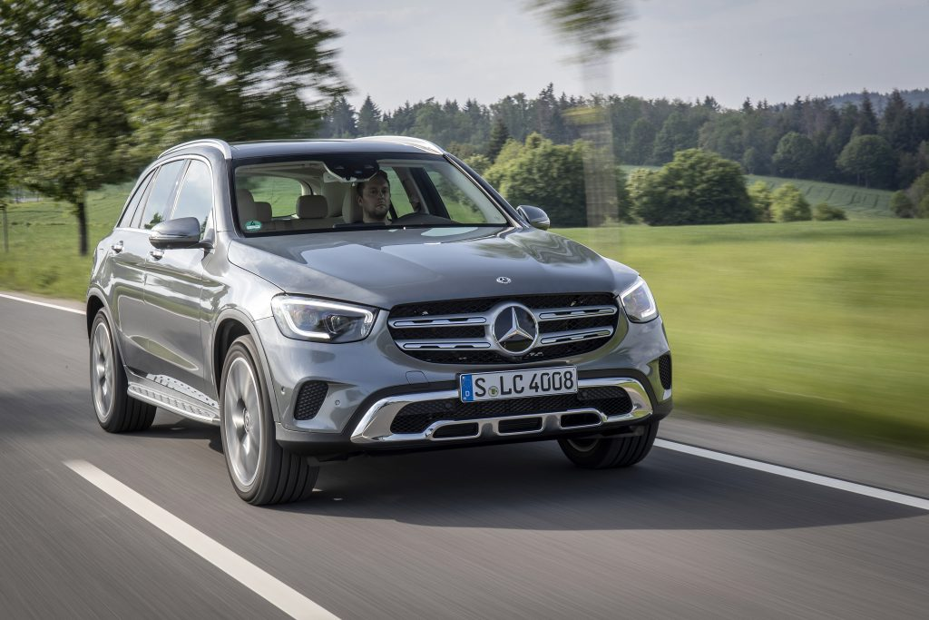 A chrome Mercedes-Benz GLC SUV driving down the road.