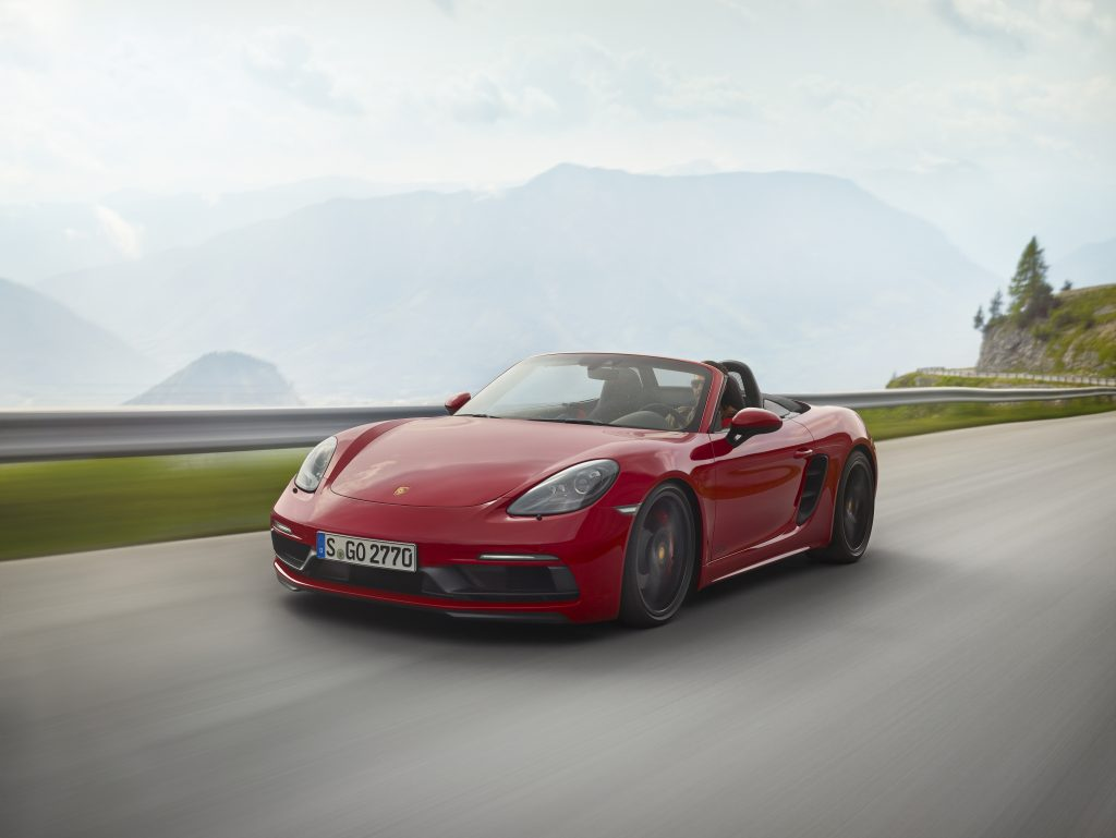 A red Porsche 718 Boxster driving down a beautiful mountain road.