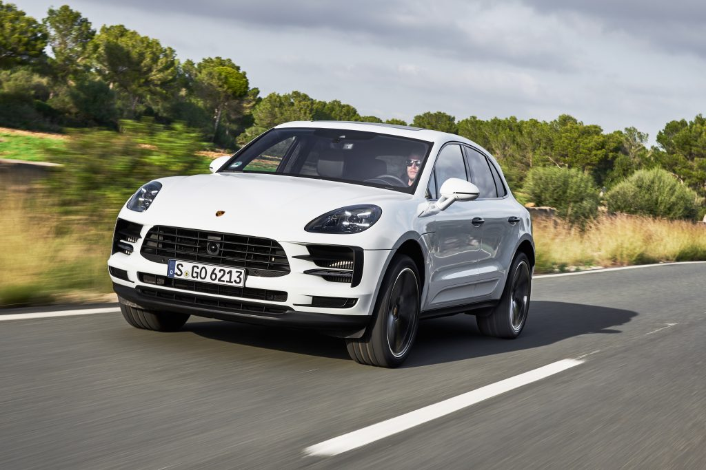 A white 2018 Porsche Macan sUV driving down the highway.