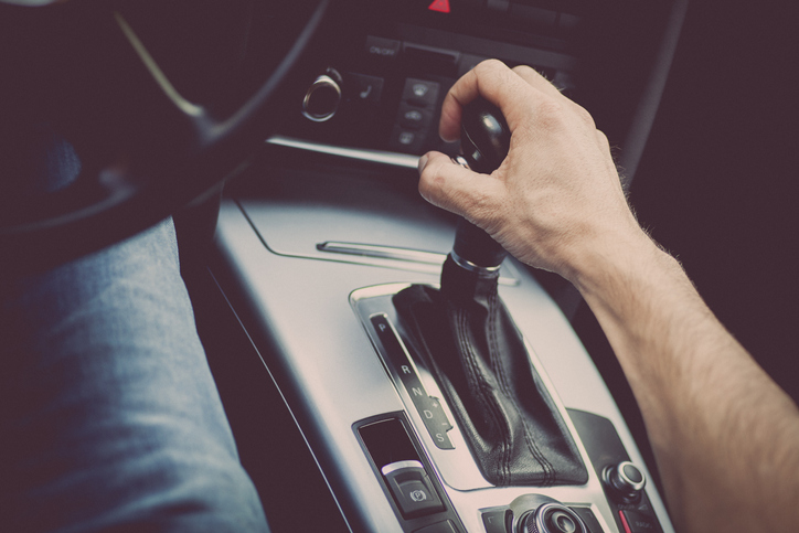 Male hand on gear shift in automatic transmission vehicle