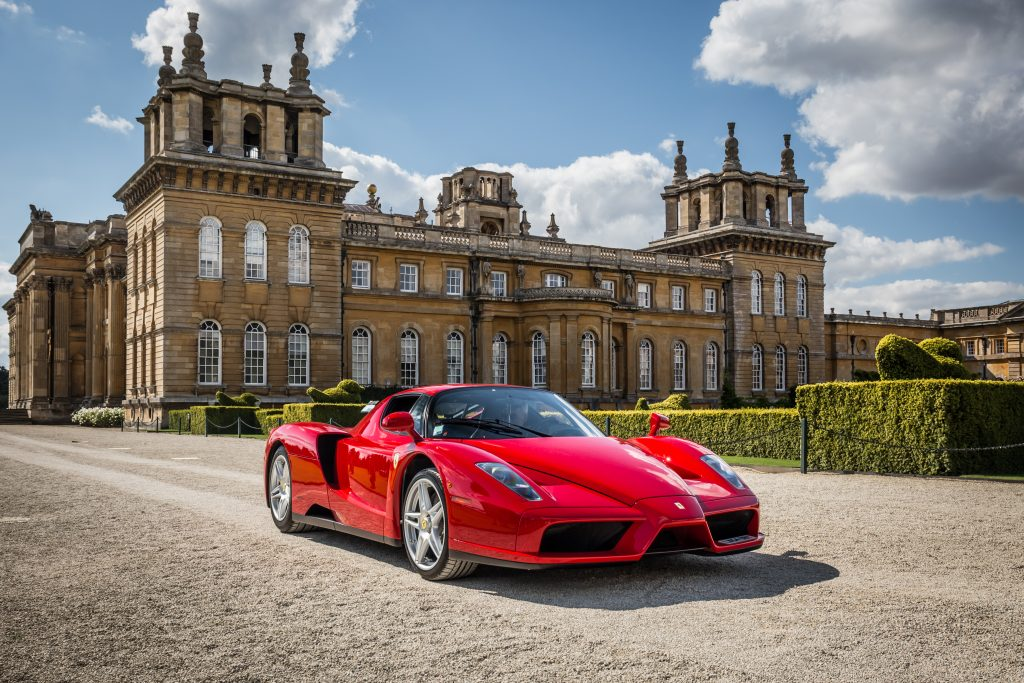 Red 2004 Ferrari Enzo parked in front of a castle