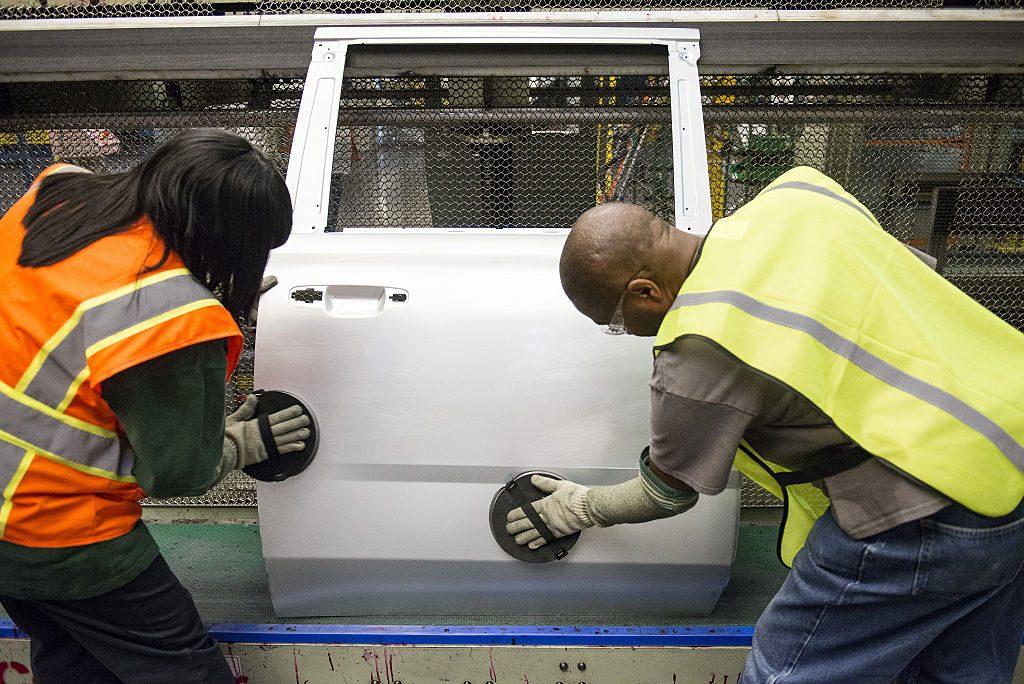 auto workers buffing car door