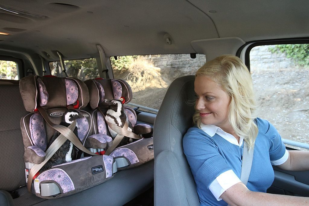 woman drives car with two car seats in the second row