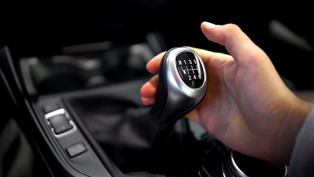 A driver manipulates the manual transmission.