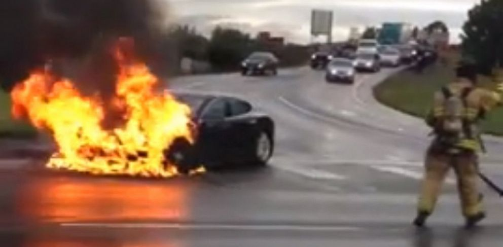 A Tesla on fire in the middle of the street