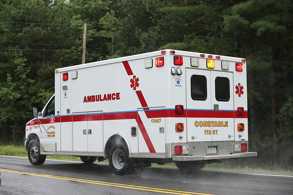 An ambulance driving down a road.