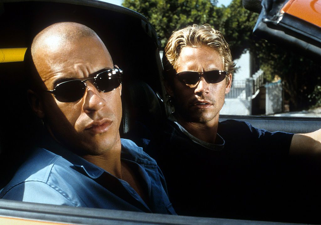 Vin Diesel And Paul Walker sitting in a car in the movie 'The Fast And The Furious'