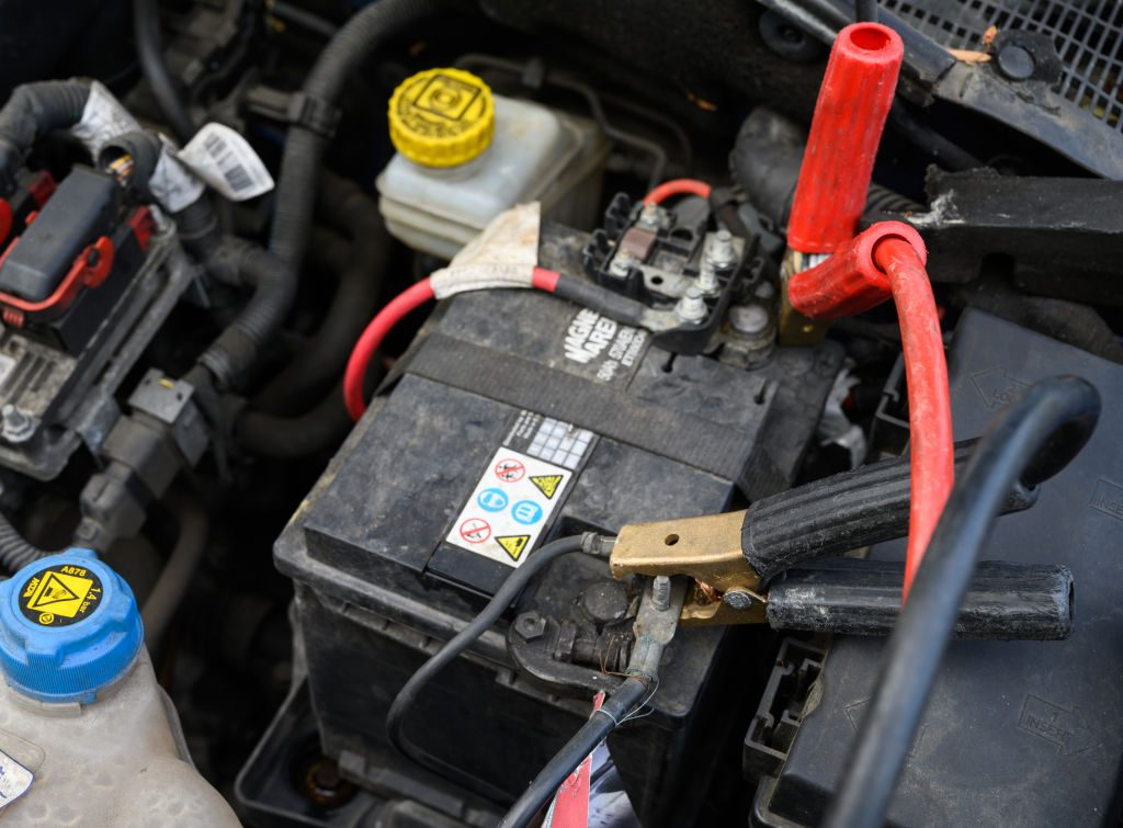 A pair of roadside emergency kit jumper cables are attached to battery terminals.