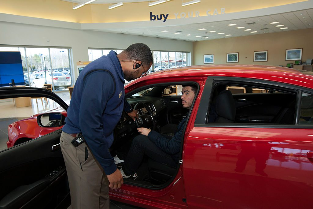 Finance and sales manager Warren Cox speaks with a customer about a Dodge Charger