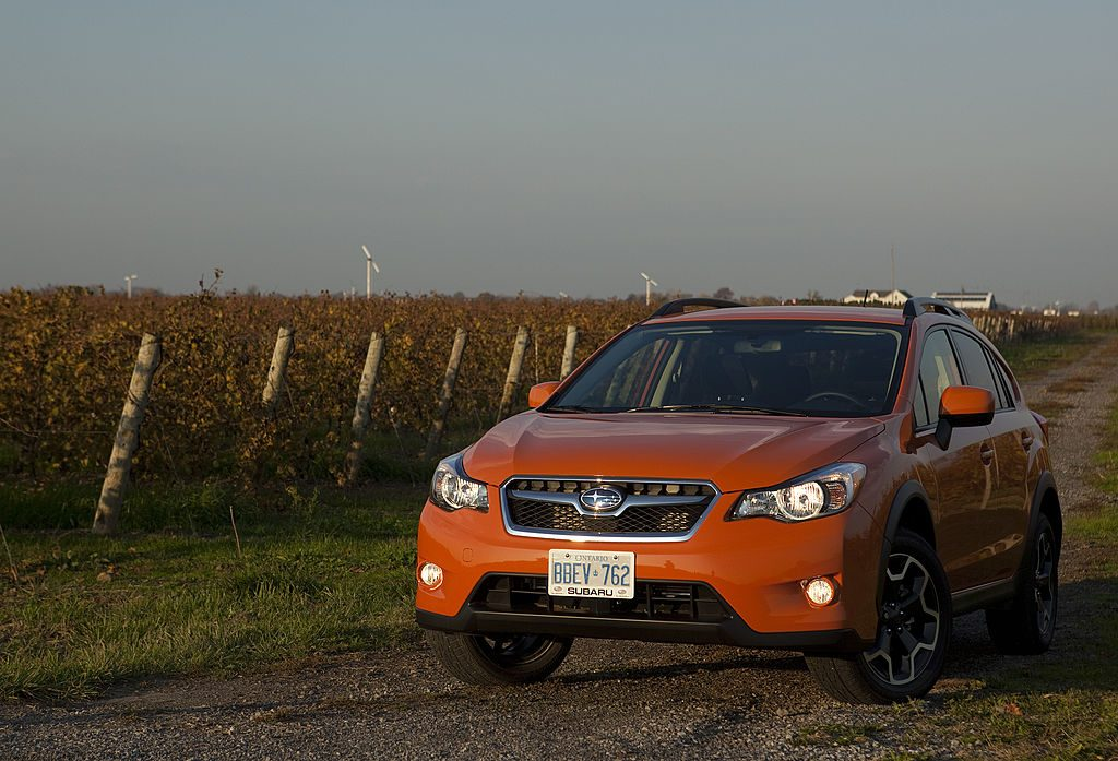 Orange Subaru Crosstrek CUV driving down a road