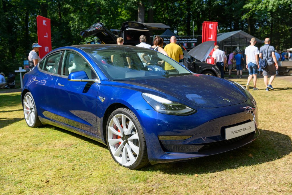 A blue Tesla Model 3 is a displayed at a car event