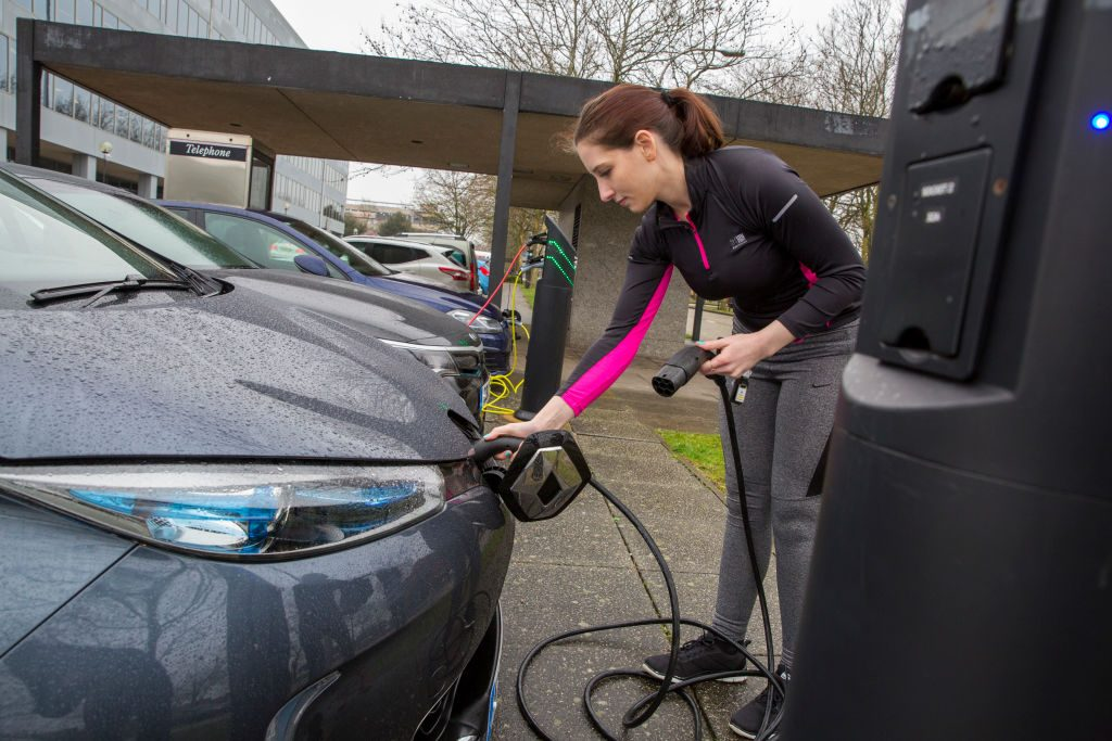 Woman charging a used electric car