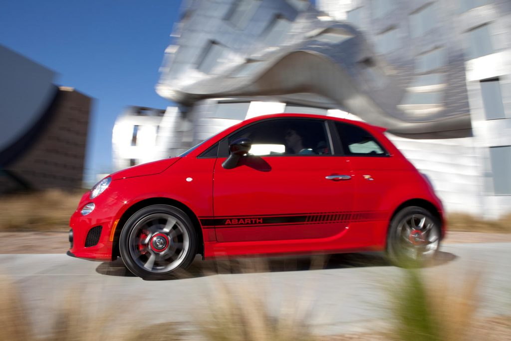 A red FIAT 500 Abarth zips around a curve.