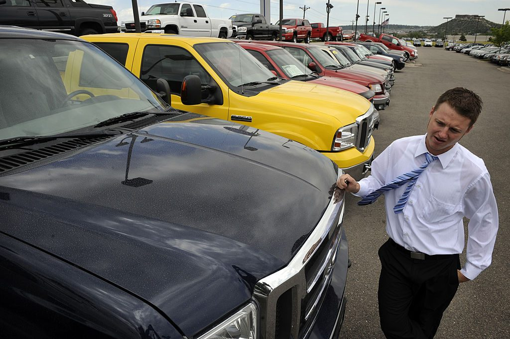 Car salesman leans against a 2005 Ford Supercab F-350 diesel truck