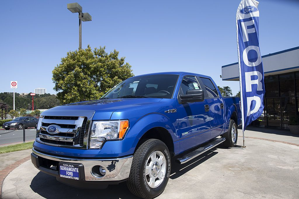 A blue 2011 Ford F-150 on a car dealership's lot.