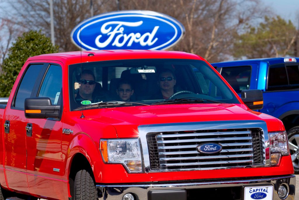 A red 2012 Ford F-150 driving off the car lot.