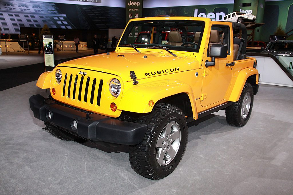 A yellow 2012 Jeep Wrangler on display at an auto show.