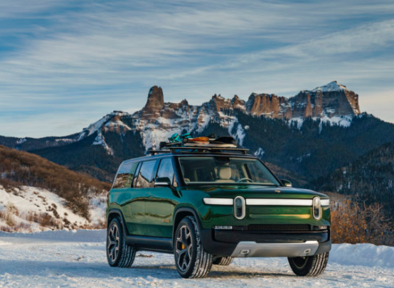 a green Rivian R1S in the snow
