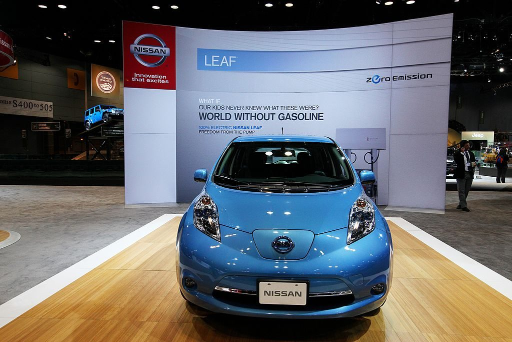 A blue Nissan Leaf on display at an auto show.