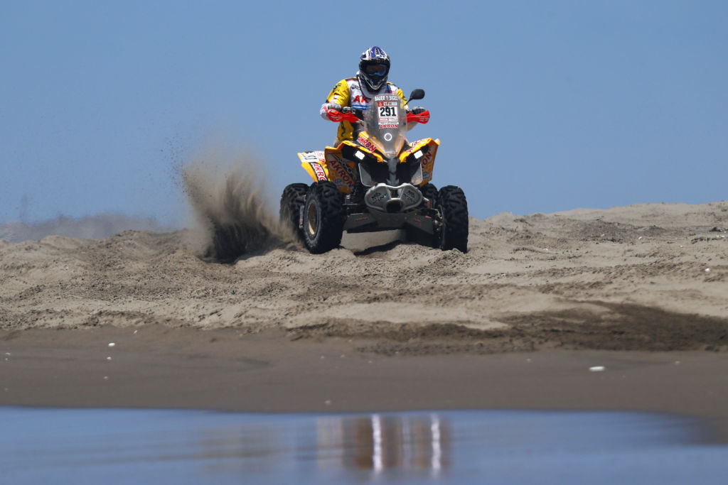 an ATV in soft sand shows someone riding hard–one reason for the most common ATV problems
