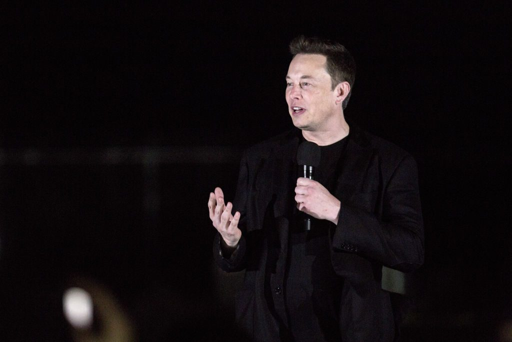 Tesla CEO Elon Musk gives a presentation on stage.