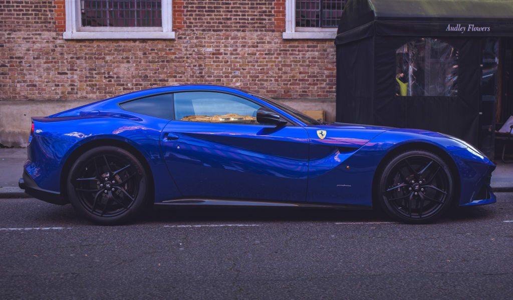 A blue Ferrari F12 Berlinetta parked on the street.