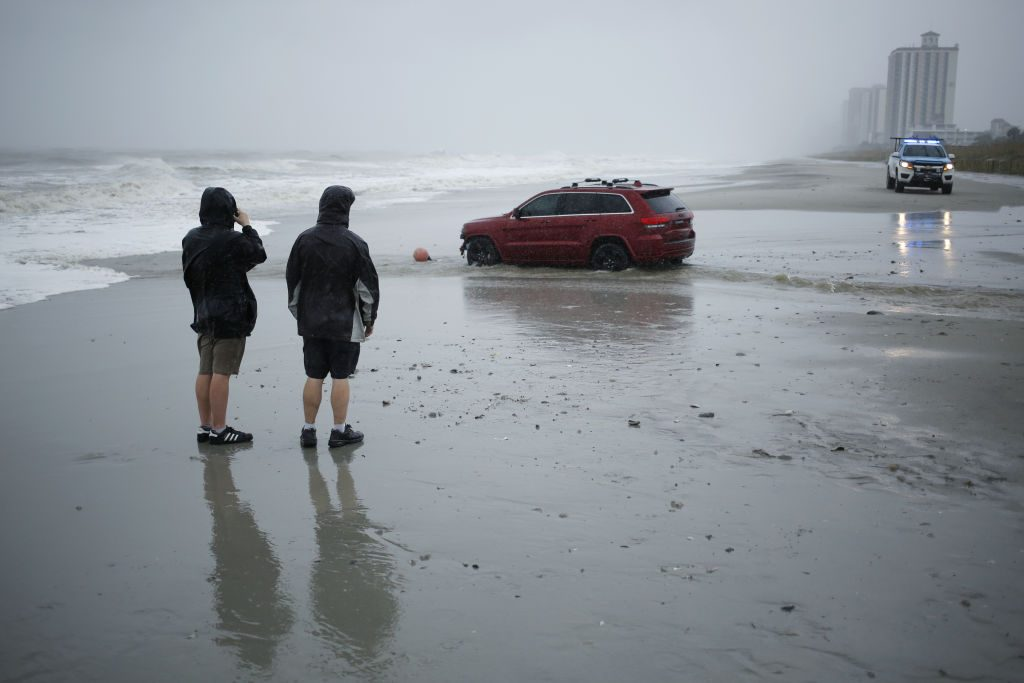 A red Jeep stranded on a beach during Hurricane Dorian